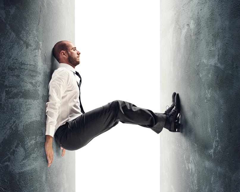 scared business man in suit falling through gap