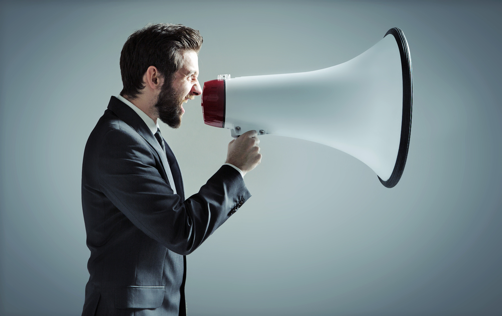 man in suit yelling into big white megaphone