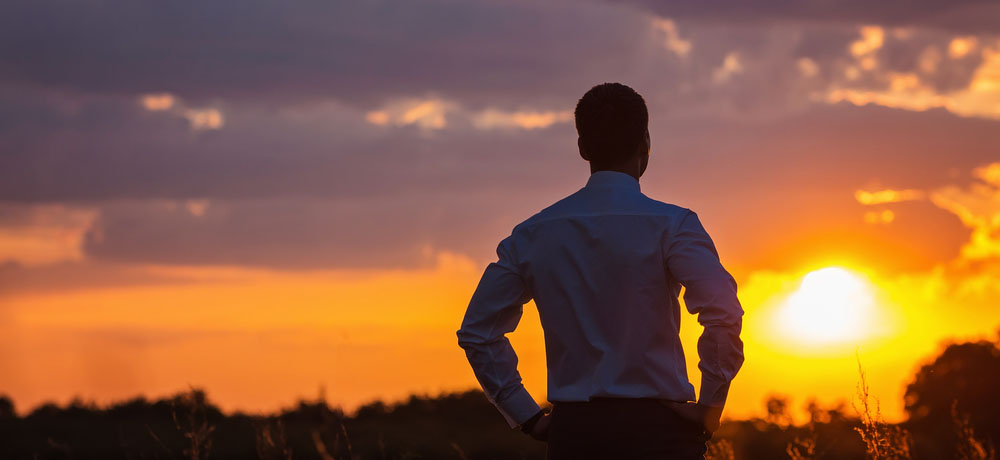 a professional practicing Mindfulness in an open field at sunset.
