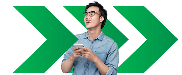 person holding mobile device while smiling in front of a background of green arrows